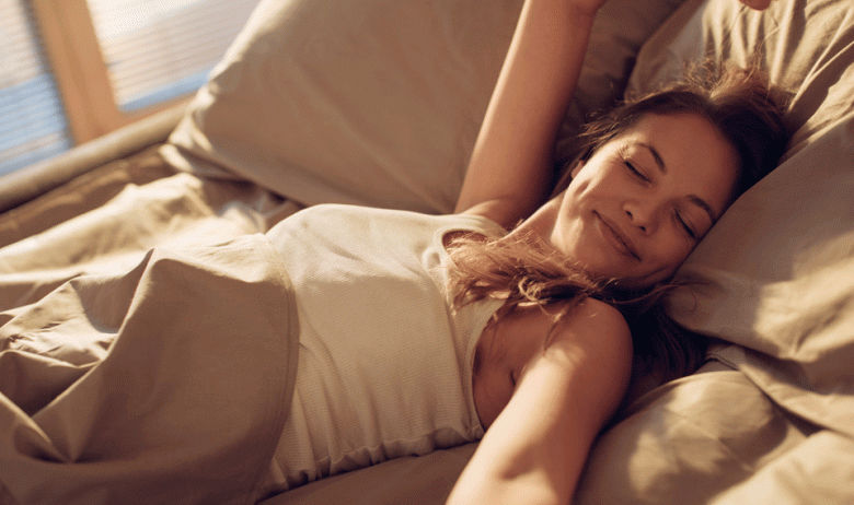 Mujer con ojos cerrados despertando feliz